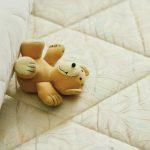Ours en peluche heureux sur un matelas / Blog Peliqan